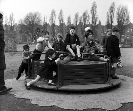 Mandatory Credit: Photo by Jon Lyons / Rex Features (573026a) Children playing on a roundabout CHILDREN PLAYING IN PLAYGROUND - 1950S